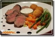 Запеченная говяжья вырезка с картофельными шариками, спаржей, морковью, пореем и соусом
